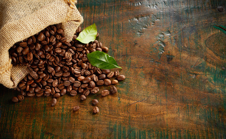 Foto de Speciality blend of fresh roasted coffee beans spilling from a hessian bag onto an old vintage wood counter with copy space - Imagen libre de derechos