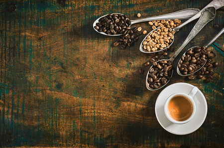 Foto de Espresso coffee with assorted roasted coffee beans displayed spilling from vintage silver spoons onto a rustic wood table with copy space viewed from above - Imagen libre de derechos