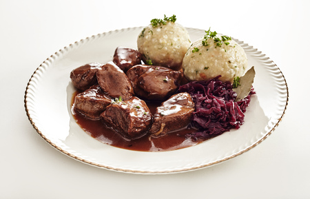 Foto de Tasty wild venison goulash in a rich gravy served with German dumplings and shredded red cabbage in a low angle view on a plate on white - Imagen libre de derechos