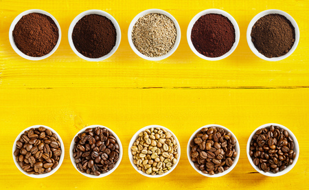 Foto de Double border of a selection of different raw and roasted beans and ground coffee in separate bowls arranged neatly top and bottom with central copy space on a yellow wood background - Imagen libre de derechos
