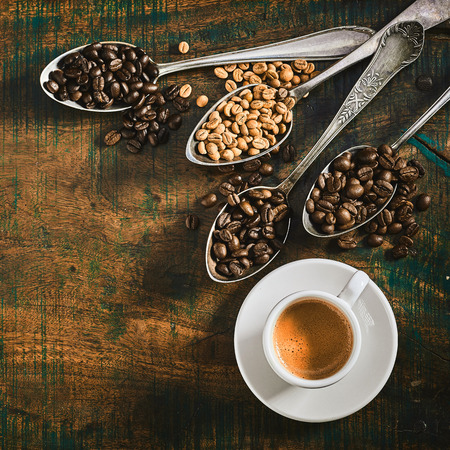 Foto de Cup of strong espresso coffee with assorted roasted and raw beans spilling over from four vintage silver spoons on a rustic wood background with copy space - Imagen libre de derechos
