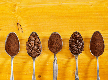 Foto de Assorted single origin coffee displayed in vintage silver spoons with roasted beans and fresh grounds over a yellow wood background with copy space - Imagen libre de derechos