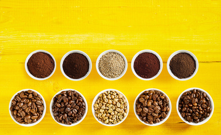 Foto de Assortment of roasted and raw coffee beans with matching grounds in bowls displayed in two rows on a yellow wood background with copy space - Imagen libre de derechos