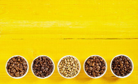 Foto de Border of an assorted variety of single origin raw and roasted coffee beans in bows on an exotic yellow wood background with copy space - Imagen libre de derechos