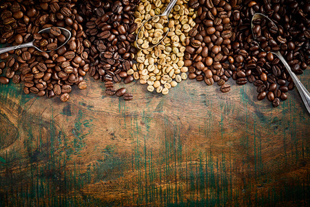 Foto de Vintage or rustic border of heaps of assorted flavors of fresh roasted coffee beans on wood with copy space - Imagen libre de derechos