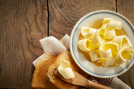 Photo pour Dish of butter curls with crispy golden toast served on a rustic wood table with wooden spreader and napkin - image libre de droit