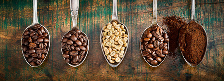 Foto de Assortment of different roasted and ground coffee beans displayed in vintage silver spoons in a panorama banner over rustic wood - Imagen libre de derechos