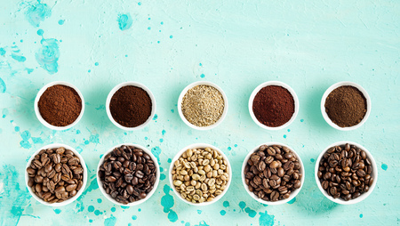 Foto de Coffee still life with roasted and raw beans and grounds neatly displayed in separate bowls in two rows on a mottled blue green background top down with copy space in banner format - Imagen libre de derechos