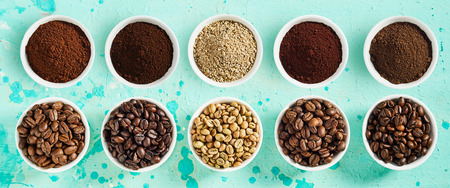 Foto de Panorama banner with assorted varieties of fresh roasted and ground coffee beans in small bowl on a mottled blue background viewed top down - Imagen libre de derechos