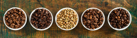 Foto de Panorama banner with assorted fresh roasted and raw coffee beans in individual bowls on rustic wood viewed top down - Imagen libre de derechos