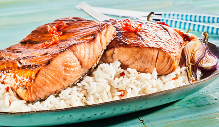 Foto de Gourmet grilled or oven-baked spicy salmon steaks with red chili on a bed of rice served with roasted onions in a close up view for a menu advertising - Imagen libre de derechos