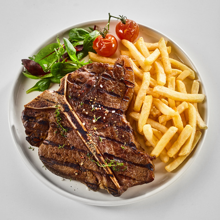 Foto de Tasty grilled or barbecued T-bone steak with fried potato chips, salad greens and roasted tomato viewed from above over white in square format - Imagen libre de derechos