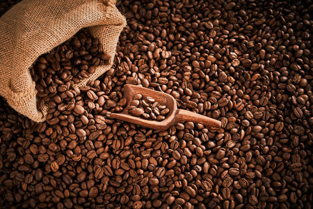 Photo for Medium roasted coffee beans spilling from a sack with wooden scoop - Royalty Free Image