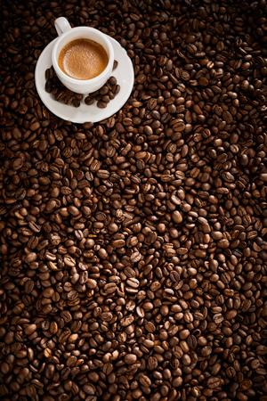 Foto de Vertical banner with roasted coffee bean background texture and a cup of frothy espresso - Imagen libre de derechos
