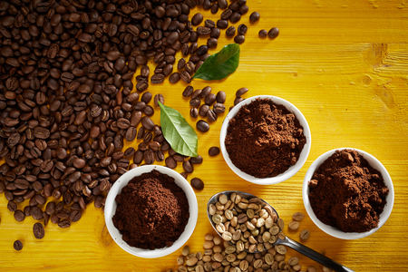 Foto de Top view of roasted and raw coffee beans with fresh grounds in small bowls - Imagen libre de derechos