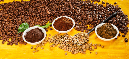 Foto de Roasted and raw beans with bowls of freshly ground coffee over a yellow wood background - Imagen libre de derechos