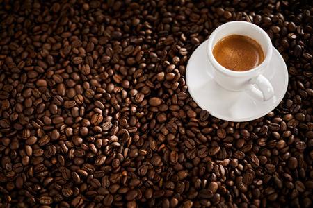 Foto de Roasted coffee bean background with a small cup of double espresso - Imagen libre de derechos