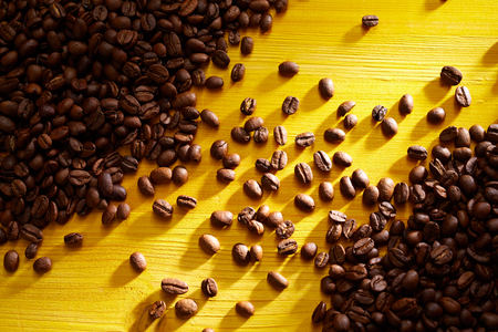 Foto de Roasted coffee beans on yellow wood background - Imagen libre de derechos