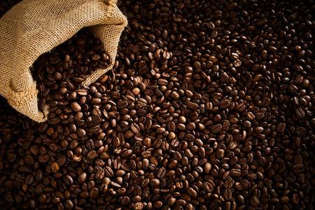 Foto de Dark roasted coffee beans spilling from a sack - Imagen libre de derechos