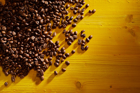 Foto de Scattered roasted coffee beans on yellow wood background - Imagen libre de derechos