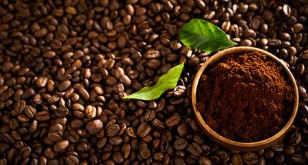Foto de bowl of freshly ground coffee on a background of roasted beans - Imagen libre de derechos