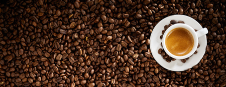 Foto de Top view of a cup of espresso coffee surrounded by roasted coffee beans - Imagen libre de derechos