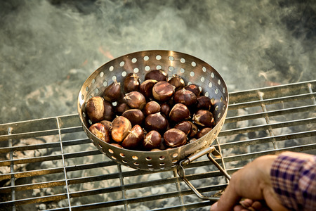 Foto de Man roasting a batch of fresh sweet chestnuts on a grill over the hot coals of a barbecue fire in a first person POV - Imagen libre de derechos