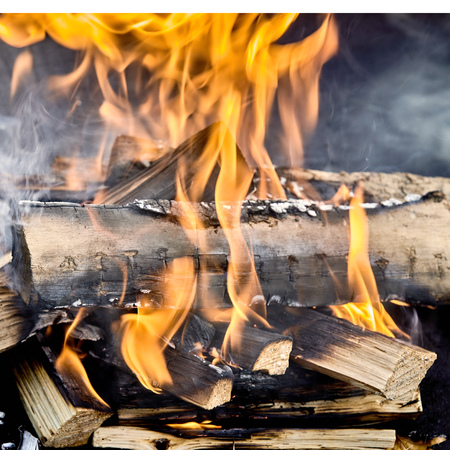 Photo for Close up on multiple flaming wooden logs burning in hot barbecue fire surrounded by clouds of grey smoke - Royalty Free Image