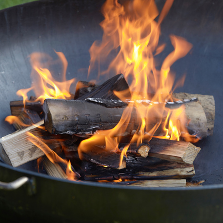 Photo for Close up on blazing logs of wood in a portable barbecue with fiery orange flames and chopped kindling below - Royalty Free Image