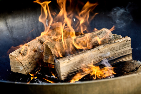 Photo for Burning logs flaming in a barbecue fire on a bed of hot coals in a close up view conceptual of an outdoor lifestyle and natural fuel - Royalty Free Image