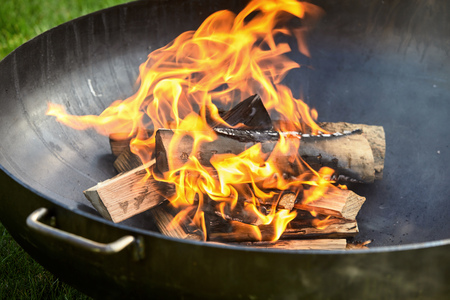 Photo for Blackened logs on fire covered in burn marks while sitting inside dark metal barbecue during cookout - Royalty Free Image