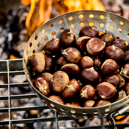 Foto de Close up on fresh fall chestnuts in their skins roasting on a fire in a metal roaster for a tasty healthy seasonal snack - Imagen libre de derechos