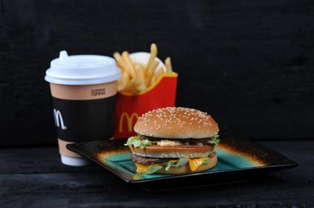 Foto de St.Petersburg, Russia - 12 August 2018: McDonald's meal on rutic black background, includes Big Mac, French Fries, Coffee cup - Imagen libre de derechos