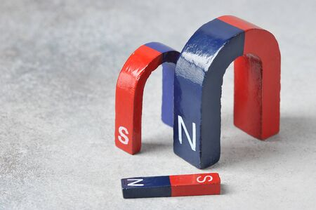 Foto de horseshoe magnet with the North and the South pole, red and blue on a gray background - device for physical experiments - Imagen libre de derechos