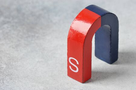 Foto de horseshoe magnet with the South pole, red and blue on a gray background - device for physical experiments - Imagen libre de derechos