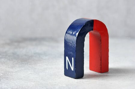 Foto de horseshoe magnet with the North pole, red and blue on a gray background - device for physical experiments - Imagen libre de derechos