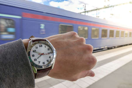 Photo pour A guy looks at his watch with a train going away in the background. Concept for hurry, miss the train / subway or be late / delayed. - image libre de droit