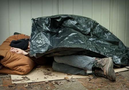 Foto de Homeless man curled up under a plastic tarpaulin, asleep on the street  - Imagen libre de derechos