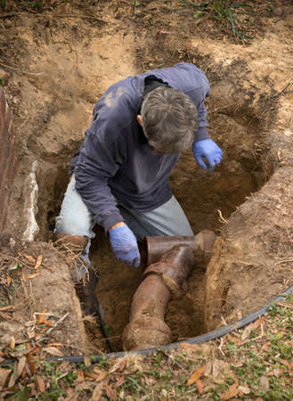Foto de Man in a hole in the earth examining old clay sewer pipes that are infested with tree roots. - Imagen libre de derechos