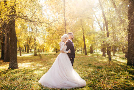 Photo for Happy bride and groom on their wedding in autumn garden - Royalty Free Image