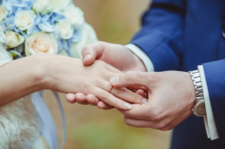 Photo pour Groom's hand putting a wedding ring on the bride's finger - image libre de droit