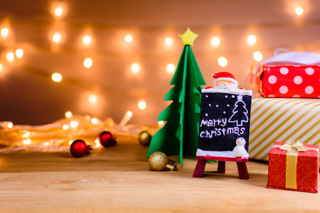 Photo for santa claus and gifts and toys on wooden boards and bokeh warm light background with Christmas holidays and happy smile kids.selective focus - Royalty Free Image