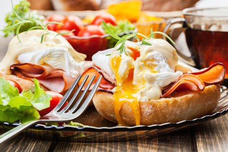 Photo for Eggs Benedict on toasted muffins with ham and sauce - Royalty Free Image