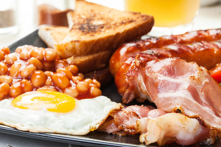 Photo for Full English breakfast with bacon, sausage, fried egg, baked beans and orange juice - Royalty Free Image