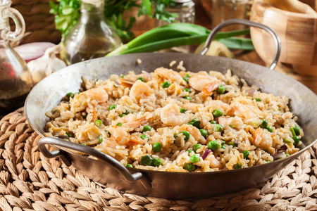 Fried rice with shrimp and vegetables on a frying pan. Popular chinese dish