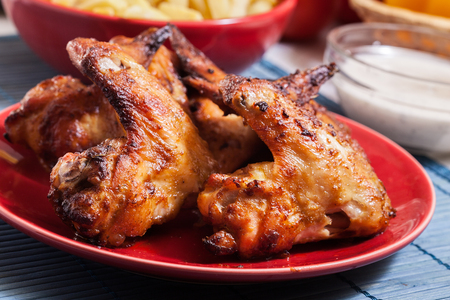 Photo for Tasty baked chicken wings on a plate served with french fries - Royalty Free Image