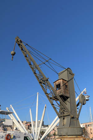 Photo for An old crane for loading cargo ships inside the ancient port of Genoa. These cranes worked until the early forties to be replaced after the war. - Royalty Free Image