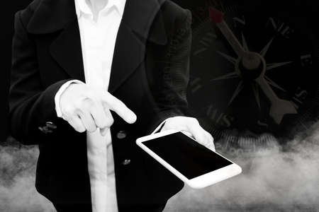 business man holding smart phone with smoke in background double exposure with compass with black and white filter