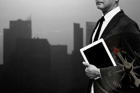 business man holding computer tablet with city light in background double exposure with compass with black and white filter