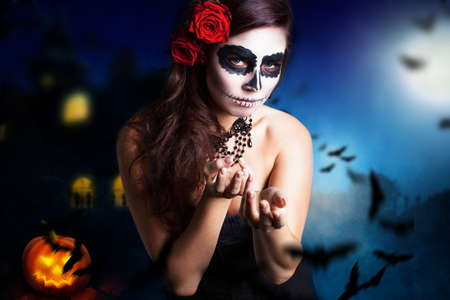 Photo pour woman with sugar skull styling in front of a halloween background  - image libre de droit